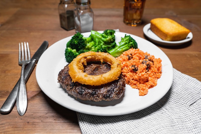 beef chopped steak with an onion ring, carrot raisin salad, broccoli, and cornbread