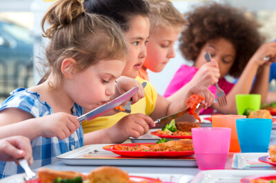 Young children eating food at a table