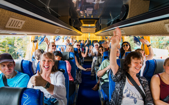Group on bus smiling with hands in the air