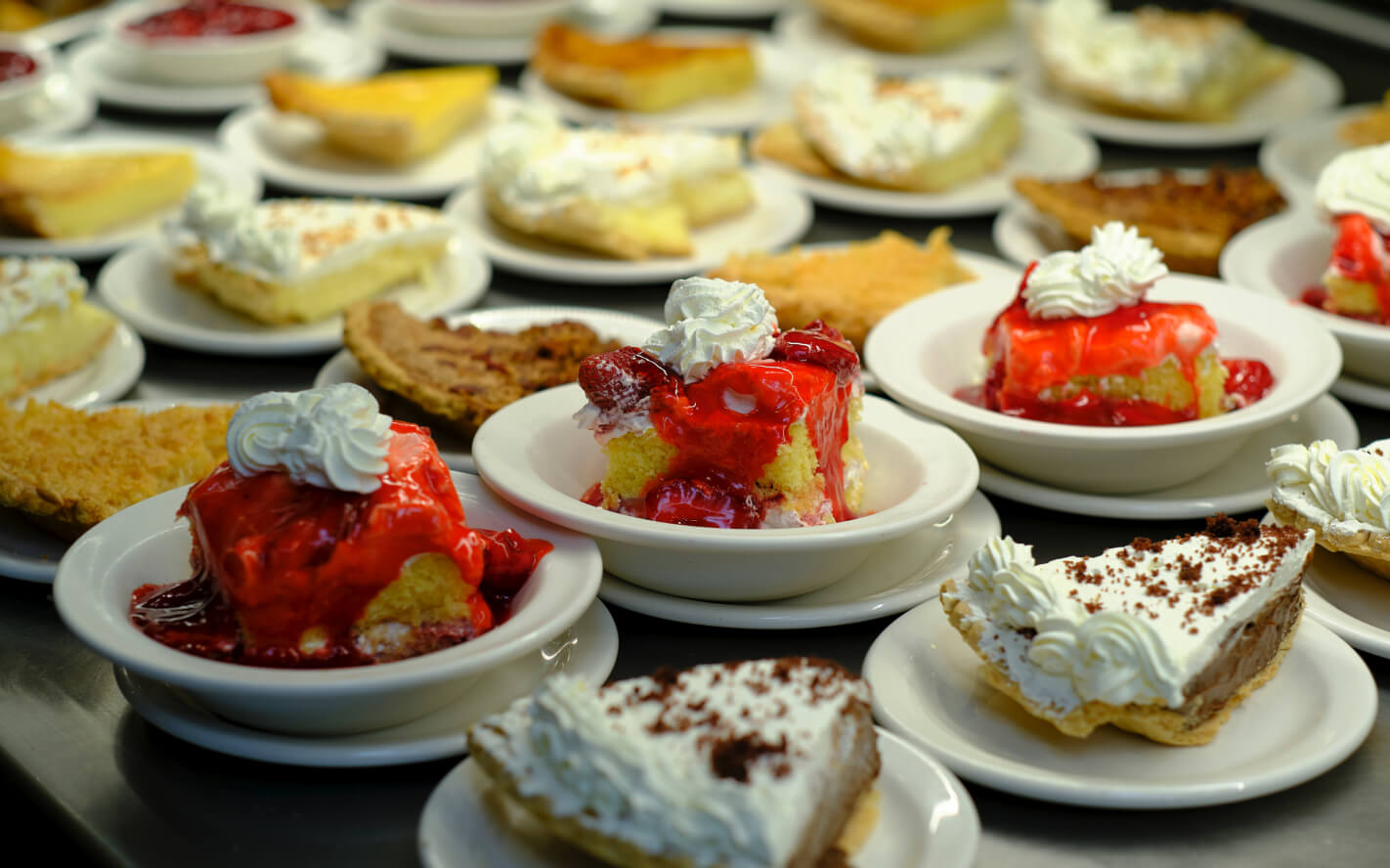 Various kinds of pie and desserts on food line