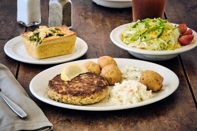 salmon pattie with hush puppies slaw and a salad